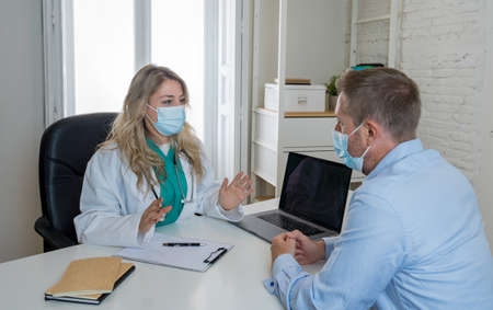 Woman doctor and male patient in face masks talking in hospital o clinic office. Female physician in medical consultation with man explaining diagnosis and treatment. Health care and Medicine.