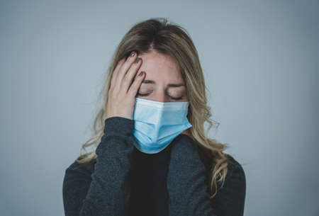 Sad depressed and worried woman with medical face mask feeling upset, distressed and sick. Young lonely woman crying suffering from depression due to coronavirus outbreak. Mental health and Covid-19.