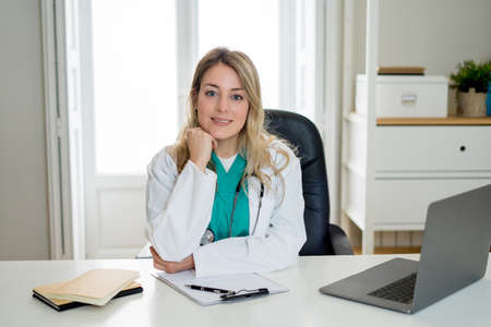 Portrait of happy attractive woman doctor working on paperwork, patient records and using laptop computer for online consultation sitting on clinic hospital office in Health care and Medical concept. Banco de Imagens