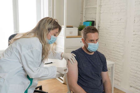 Female doctor or nurse vaccinating young man in clinic. Male Patient Getting Vaccinated Against Coronavirus Receiving covid Vaccine Intramuscular Injection During Doctor's Appointment In Hospital.