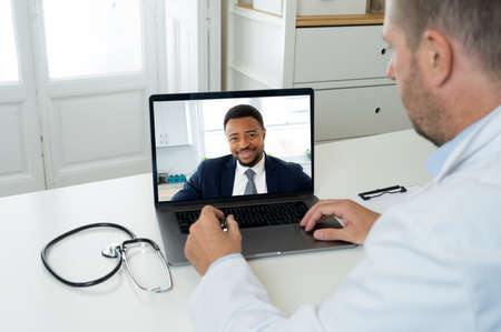 Screen laptop with afro american man video calling physician for medical advice or treatment. Medical student studying medicine in online video conference with doctor. Health care and e-learning. Banco de Imagens