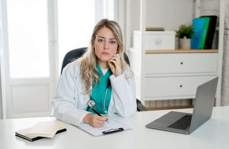 Portrait of successful attractive woman doctor in white coat working on patient medical records on laptop computer and online consultation in hospital office for Health care and Medical insurance.