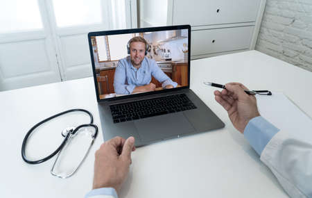 Screen laptop with caucasian man video calling physician for medical advice or treatment. Medical student studying medicine in online video conference with doctor. Health care and e-learning. Banco de Imagens