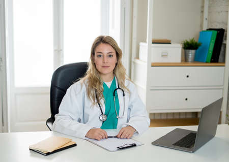 Portrait of happy attractive woman doctor in white coat working with laptop computer and writing on paperwork sitting on clinic hospital office desk in Health care and Medical insurance concept.