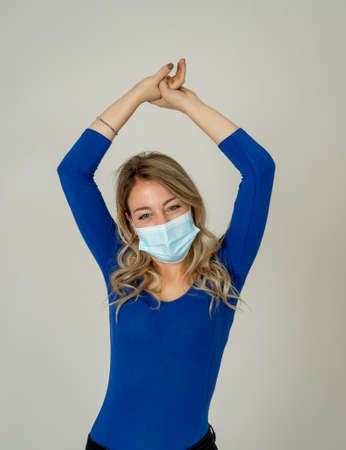 Close-up portrait of young attractive woman wearing protective medical face mask isolated over neutral background. Millennial female in face cover against the spread of coronavirus, Covid-19.