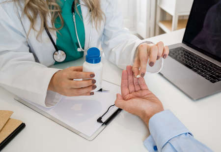 Young attractive caucasian woman doctor holding a jar of pills explaining prescription and medical treatment to female patient. Health care, Medicine and pharmacy concept.