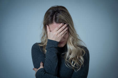 Portrait of young attractive caucasian woman suffering from depression, stress and anxiety. Sad and lonely woman crying, feeling depressed, distressed, worried and overwhelmed. Mental Health care. 免版税图像