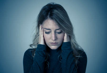 Portrait of a young attractive caucasian woman suffering from depression, stress and anxiety. Sad and lonely woman crying, feeling depressed, distressed, worried and overwhelmed. Mental Health care.