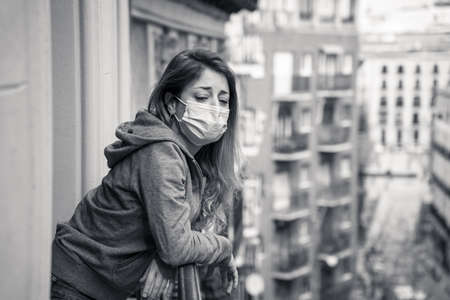 Unhappy young woman in her 20s or 30s feeling sad and lonely in quarantine while infected with coronavirus. Depressed woman with protective face mask with COVID-19 in isolation at home.