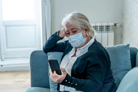 Lonely sad senior woman in face mask feeling scared, hopeless and depressed, worried about husband at hospital infected with coronavirus .Checking mobile phone for news. Anxiety, fear and COVID-19. 免版税图像