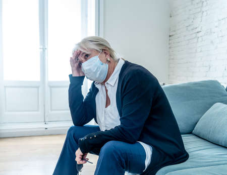Lonely and sad senior woman in face mask feeling scared, hopeless and depressed, worried about husband tested positive for coronavirus. Elderly grieving the lost of the loved one due to COVID-19.