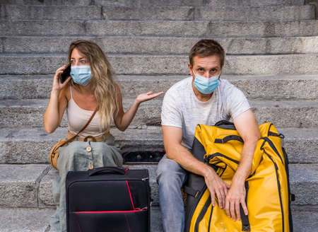 Sad tourist couple with mask and luggage ready for summer vacations trip worried   test results and immunity passport. Vacations cancellations due to post pandemic  travel restrictions.