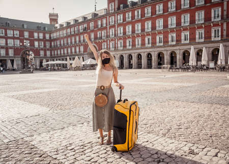 Happy Tourist in madrid, Spain Europe,   Woman wearing face mask taking selfie happy to be able to travel over the summer.