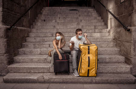 Sad tourist couple with mask and luggage ready for summer vacations trip worried about  test results and immunity passport.