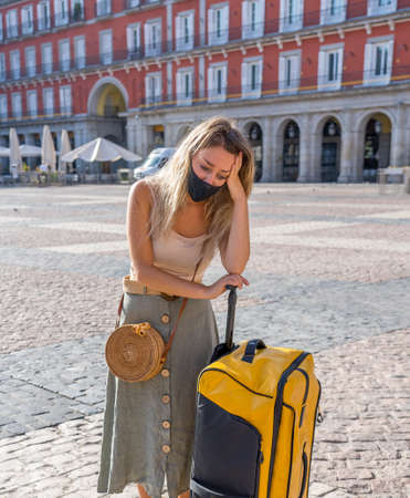 Summer Travel during pandemic and tourism. Sad Tourist woman with luggage and facemask could not get abroad over summer holidays.