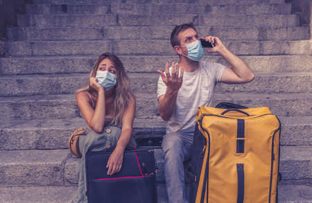 Sad tourist couple with mask and luggage ready for summer vacations trip worried about virus test results and immunity passport.
