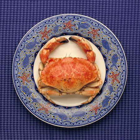whole cooked crab on decorative plate