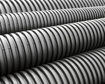 Stack of black spiral storm sewage drain pipes
