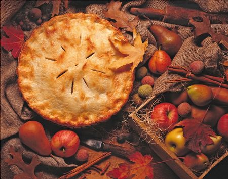 whole apple pie surrounded with fruit and autumn leaves Stock Photo