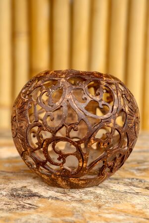 Coconut shell carving. Handicraft of indigenous people in Bali, Indonesia. Shelve with balinese souvenirs - ornamental shell for candle wich are carved from the coconut. Traditional product of Bali.