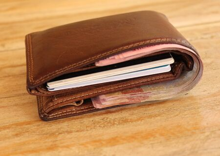 Brown leather wallet full of banknotes and credit cards. Men's wallet on a wooden table. Money in a closed brown purse. Best background for your project.