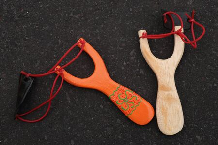 Couple of simple wooden slingshot isolated. Orange and natural wooden handle with two red rubber bands attached to a black leather strip used to put things to be shot on black background. Primitive but effective weapon.