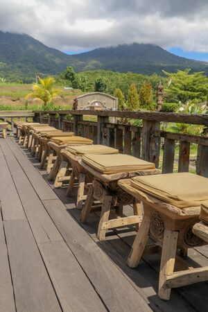 Row of wooden stools with cushions on terrace with floor made of planed wooden planks. It bumps from roughly worked beams. Background with mountains whose peaks are shrouded in thick clouds. Sunny day.