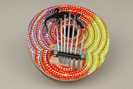 Traditional musical instrument karimba with gecko lizard motif. Close up of calimba made from coconut shell. Details of a thumb piano (Kalimba, Mbira) with silver tines.
