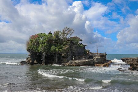 Waves shatter on a cliff at the top of which is the Hindu temple of Tanah Lot. Temple built on a rock in the sea off the coast of Bali island, Indonesia. Lush tropical vegetation on top of a cliff.