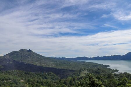 Volcano landscape with lava fields, pine tree forest and farms and houses on the slopes. Kintamani is a village on the western edge of the larger caldera wall of Gunung Batur in Bali, Indonesia. Stock Photo