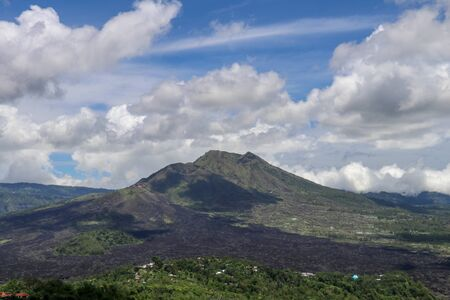 Volcano landscape with lava fields, pine tree forest and farms and houses on the slopes. Kintamani is a village on the western edge of the larger caldera wall of Gunung Batur in Bali, Indonesia. Stock fotó