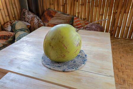 Young green coconut on teak table. Whole coconut with bamboo background and pillow. Healthy tropical fruit from coconut palm. Fresh coconut water. Zdjęcie Seryjne