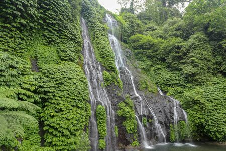 Secret jungle waterfall cascade in tropical rainforest with rock and turquoise blue pond. Banyumala twin waterfall in mountain slope in Bali, Wanagiri, Indonesia. Nature water slide waterfall. Imagens