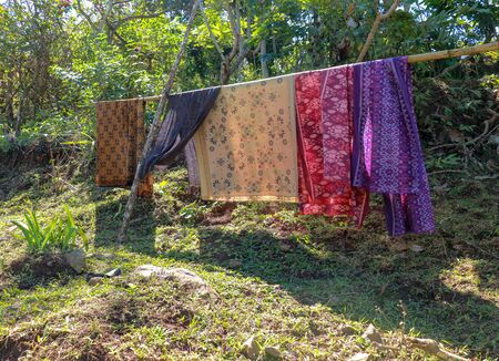 Sarong or Sarung is a traditional outfit worn by Hindus in Bali Island during ceremonies. Colored fabrics draped over the bamboo trunk are dried in the sun. Suspended washed laundry.