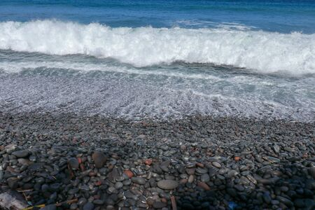 Tropical beach with black pebbles. The island of Bali with a rocky coast. black sand beach Indonesia.