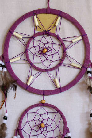 Red black and purple Dreamcatcher with bat made of feathers leather beads and ropes, hanging on the white background. Foto de archivo