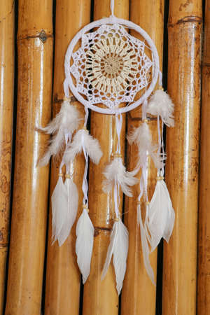 White crocheted dreamcatcher, an Indian amulet that protects the sleeper from evil spirits and diseases. Soft focus. Closeup.
