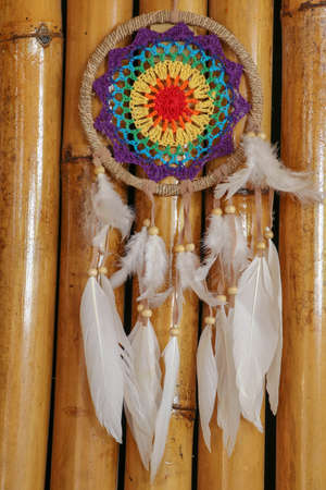 Beautiful multicolored handmade dreamcatcher on natural bamboo background.