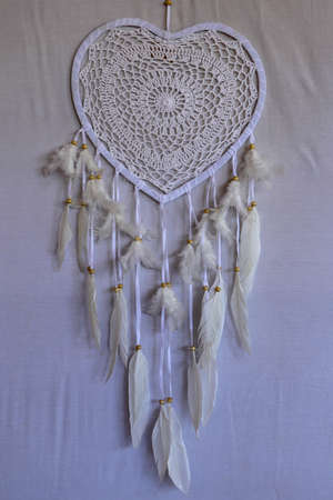 Dream catcher shaped heart with beige peacock feathers in the interior.