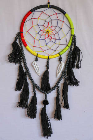 Beautiful multicolored handmade dreamcatcher with sea shells on white background.