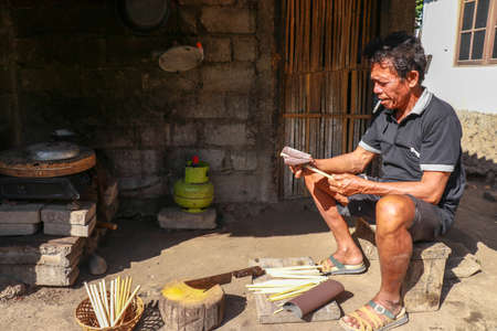 Old man working with bamboo in his workshop to make bamboo straws, Bali, Indonesia. Ecological way of producing recyclable products. Front view to a worker who makes bamboo straws Archivio Fotografico