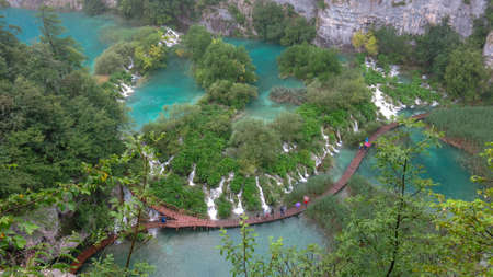Tourists on the wooden park pathways enjoying the view of emerald lakes, cascades and crystal clear water, Plitvice Lakes National Park, Croatia. Stock Photo