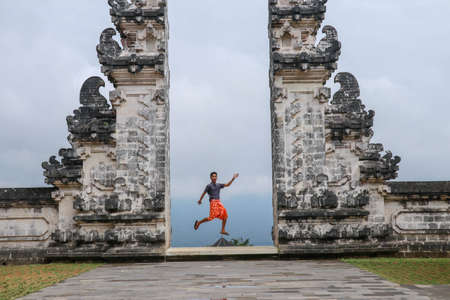 Bali, Indonesia. Young taveler man jumping with energy and happiness in the gate of heaven. Lempuyang temple.