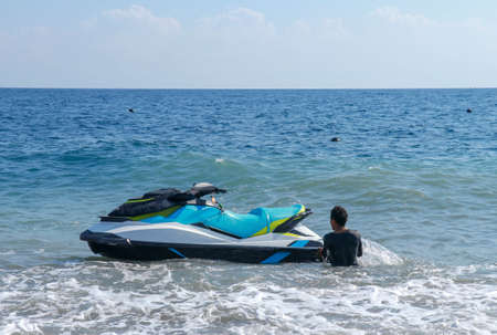 Jetski floating on blue sea water. Strong power watercraft is waiting customers. Young Indonesian holding a jetbike near the shore. Stockfoto