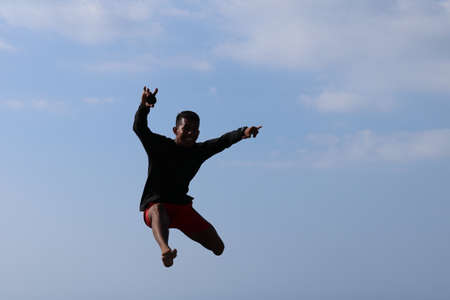 Happy han jumping above blue sky background. Young cheerful Indonesian jumps. A teenager in a good mood jumps in the air. Sunny tropical day. Archivio Fotografico