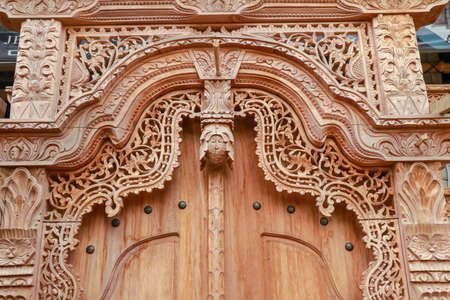 Balinese wood carved doors with traditional local ornaments. Local traditions and craftmanship concept