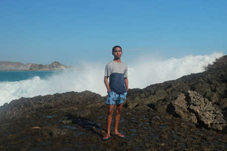 Waves hitting round rocks and splashing. A young man stands on a rocky shore and the waves crash against a cliff