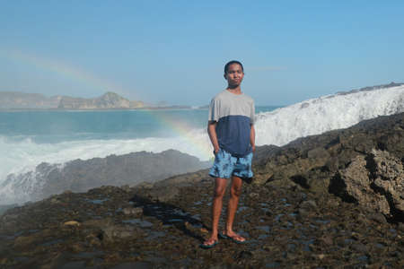 A man stands on a rocky shore and the waves crash against a cliff. Rainbow phenomenon in water fog. Waves hitting round rocks and splashing Archivio Fotografico