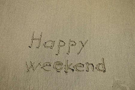 happy weekend written on a tropical white sand beach Banco de Imagens