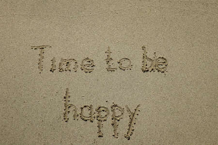 time to be happy, happiness concept. The sign written on sand